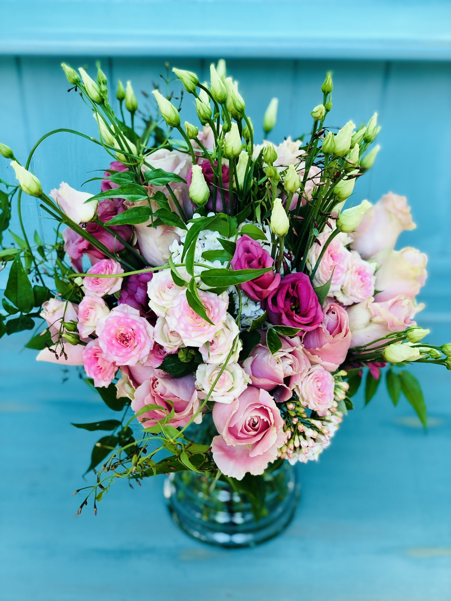 Luxury summer pink and blue bouquet of pink avalanche roses, bouvardia, clematis and agapanthus.